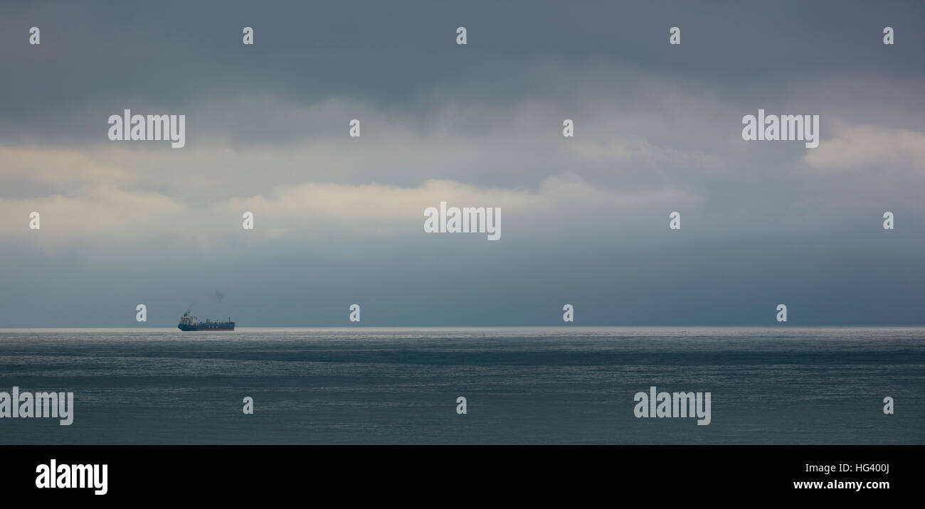 Grey cloudy seascape with one ship on the horizon near Formia on the Mediterranean coast of Lazio, Italy. - Stock Image
