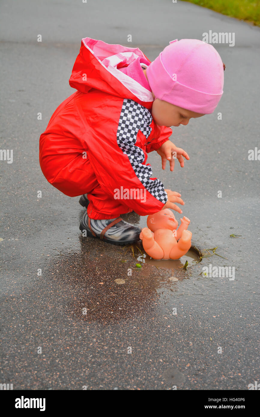 A walk of a little girl with a doll after a rain. - Stock Image
