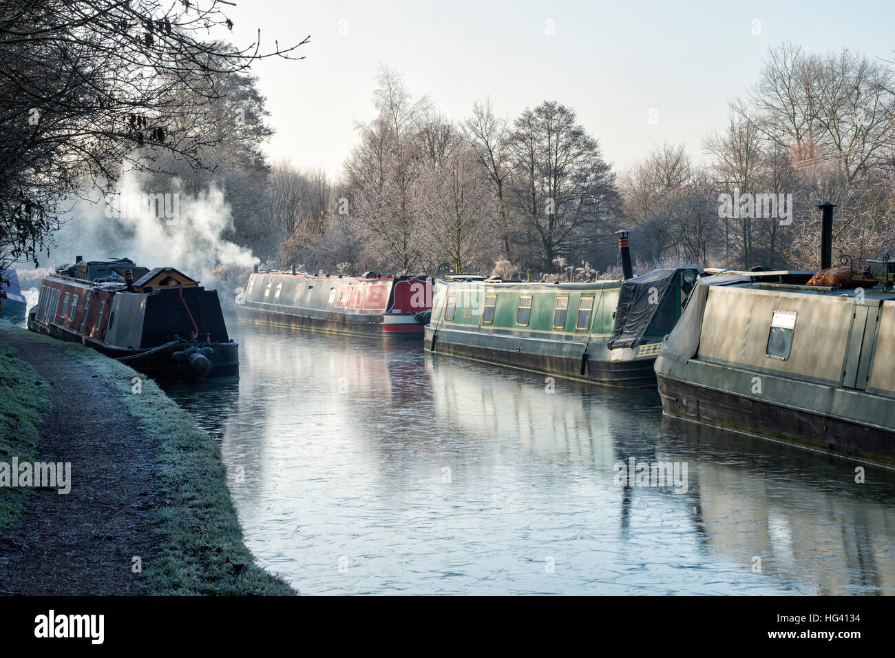 Canal boat with smoking chimney on the oxford canal on a frosty December morning. Cropredy, Oxfordshire, England - Stock Image