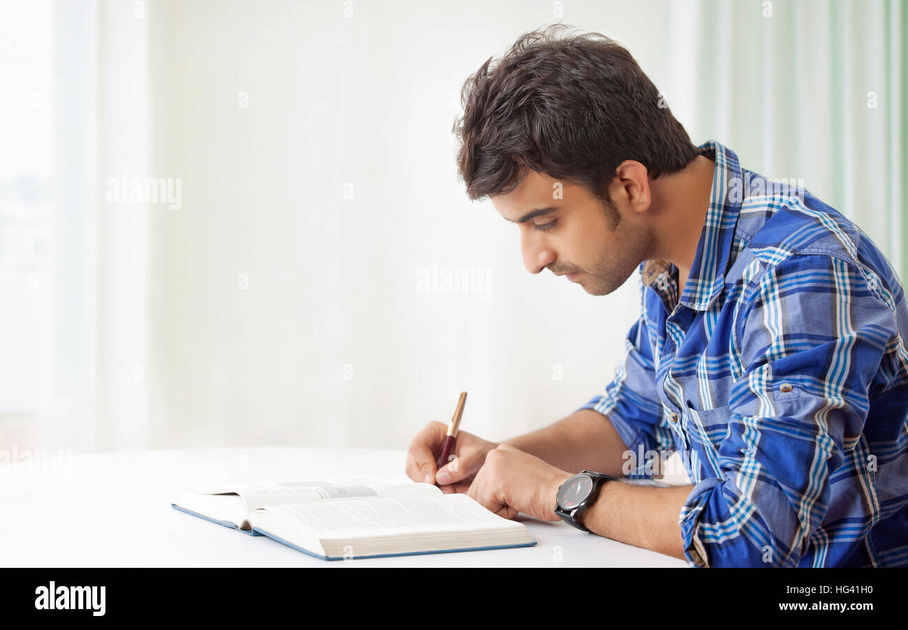 Young man studying and making notes - Stock Image