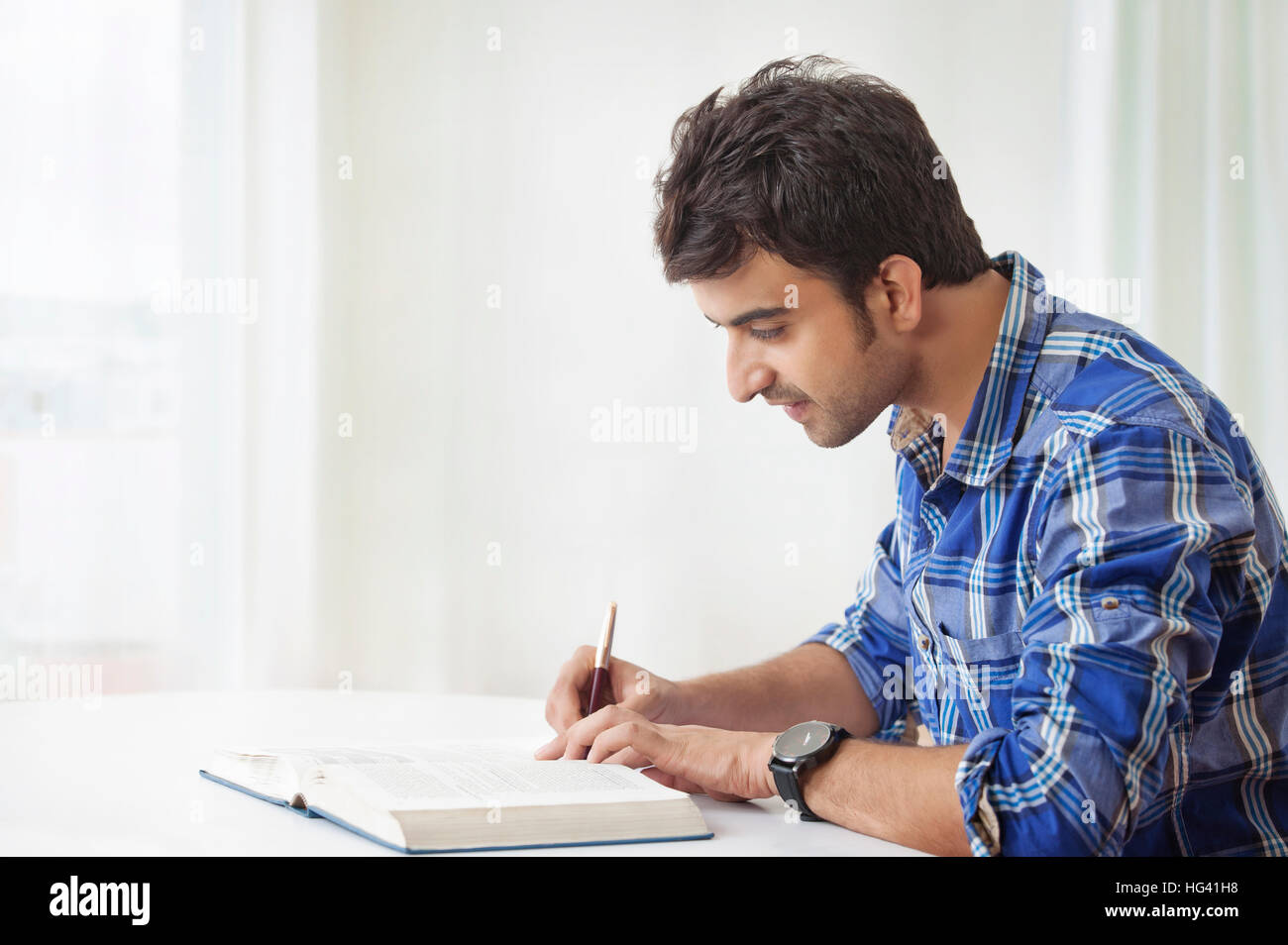 Young man studying and making notes Stock Photo