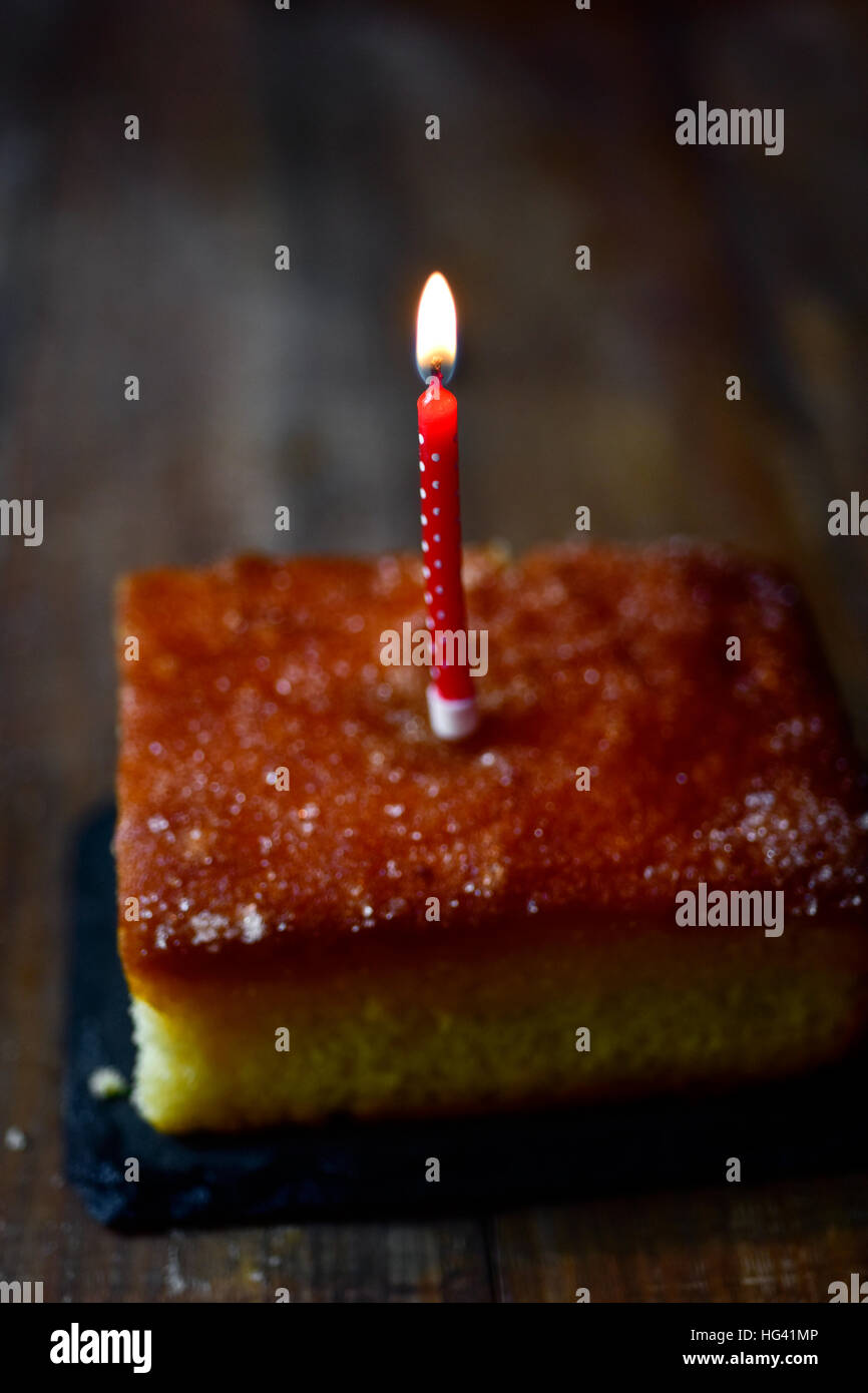 closeup of a cake topped with a lit birthday candle on a rustic wooden table - Stock Image