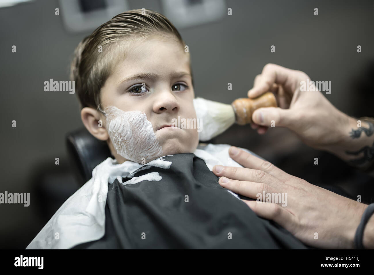 Humorous shaving of little boy - Stock Image