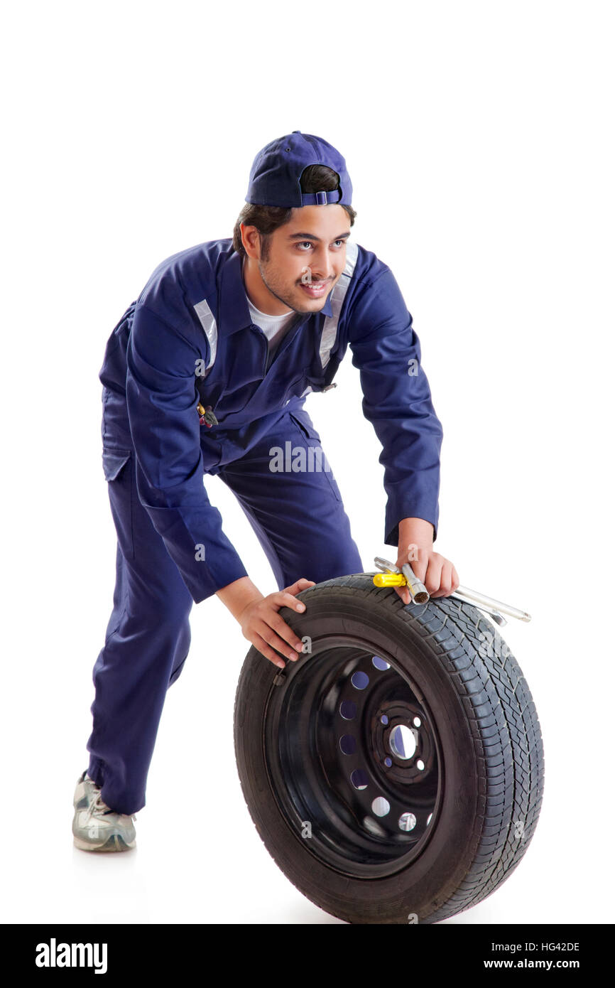 Portrait of car mechanic with spare tyre and hand tools - Stock Image