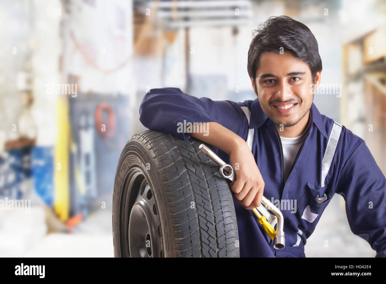 Portrait of car mechanic with spare tyre and hand tools in garage - Stock Image