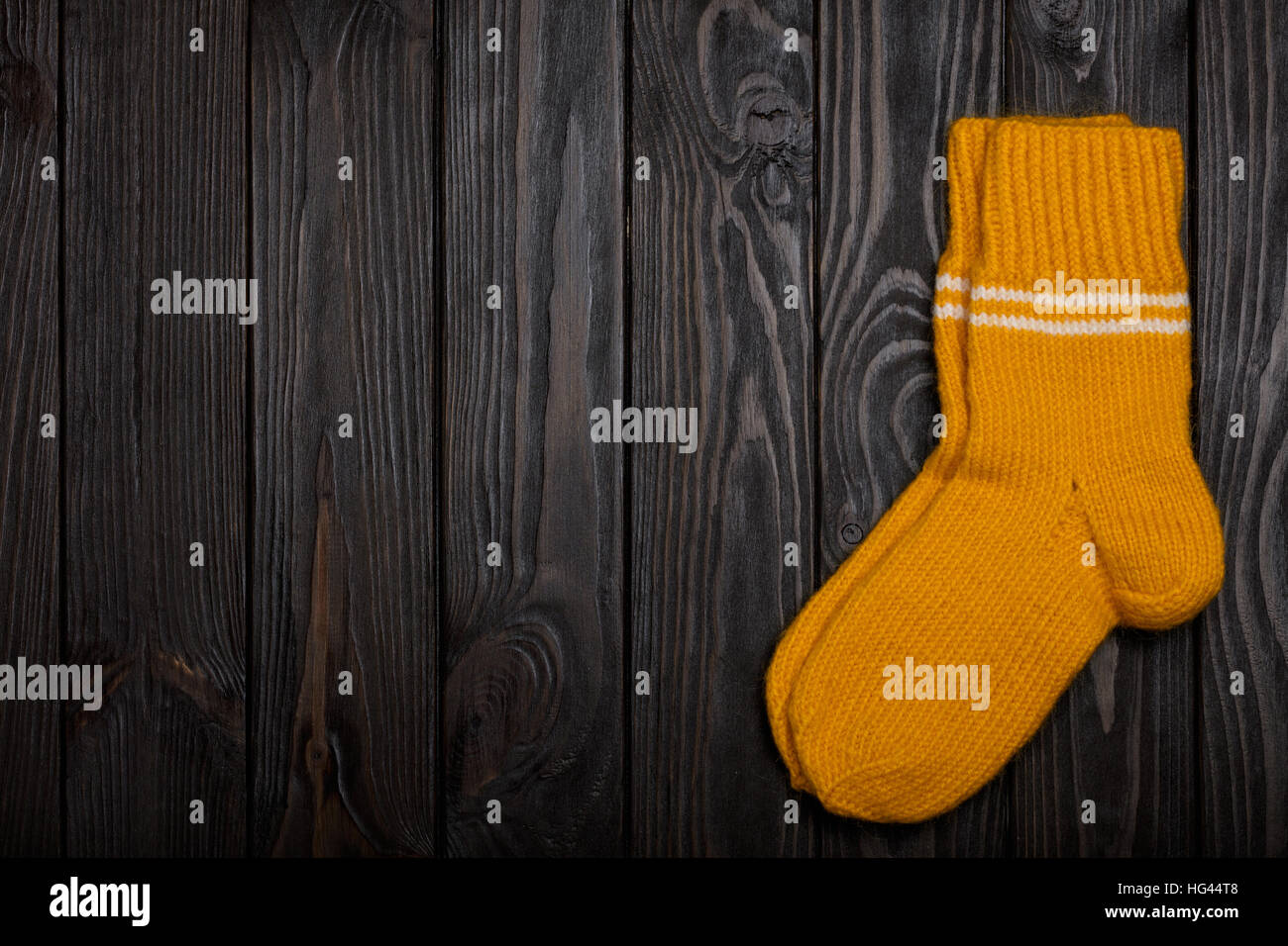 Knit yellow wool socks on dark wooden background. - Stock Image