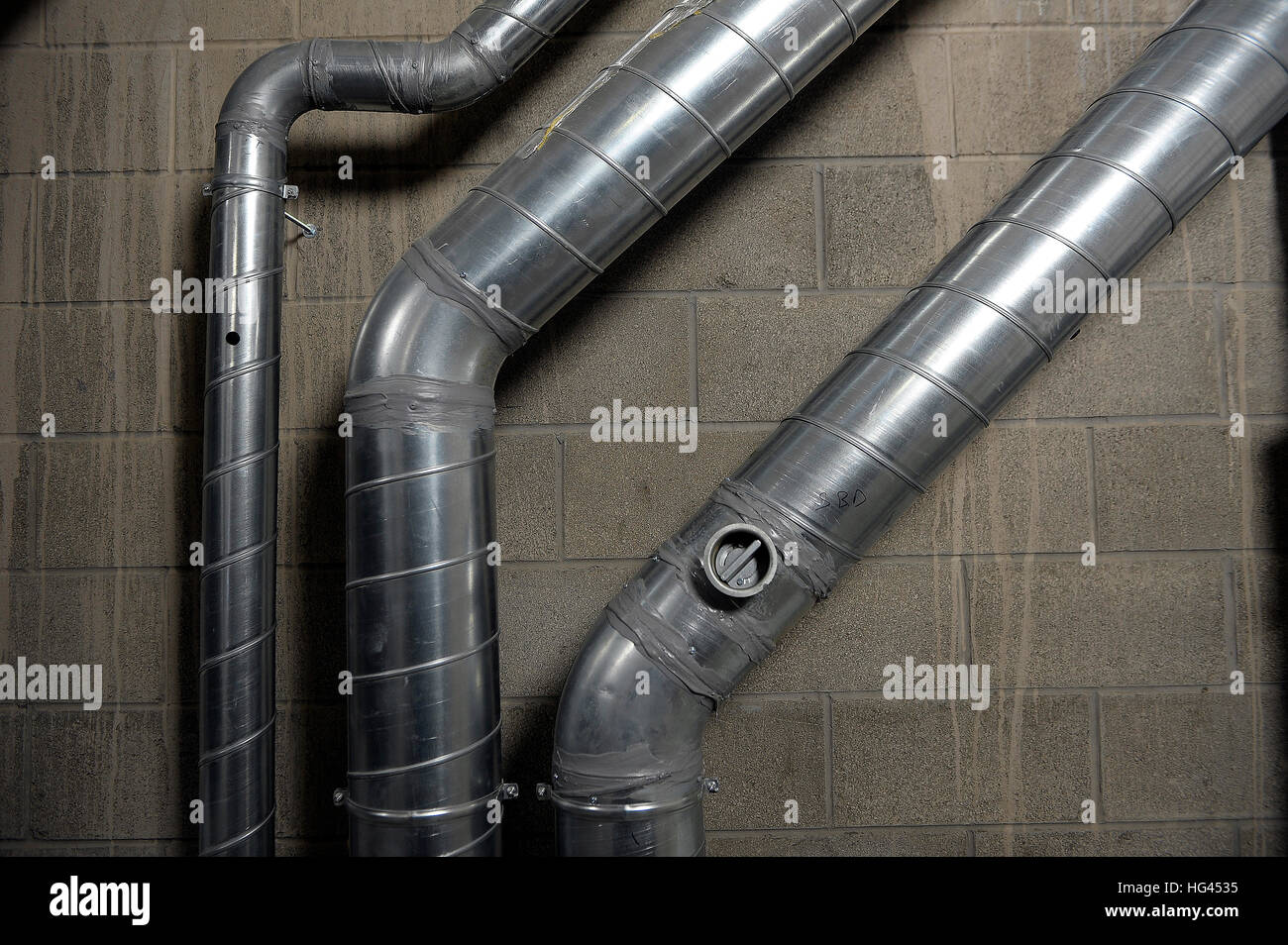 Industrial aluminium air conditioning pipes mounted on a breeze block wall. - Stock Image