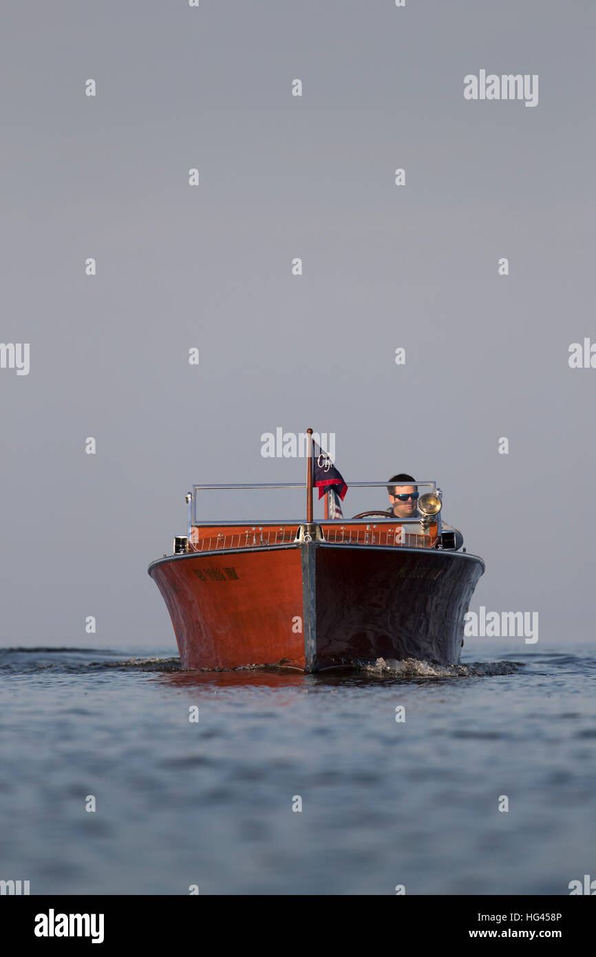 A slowly approaching wooden speedboat. - Stock Image