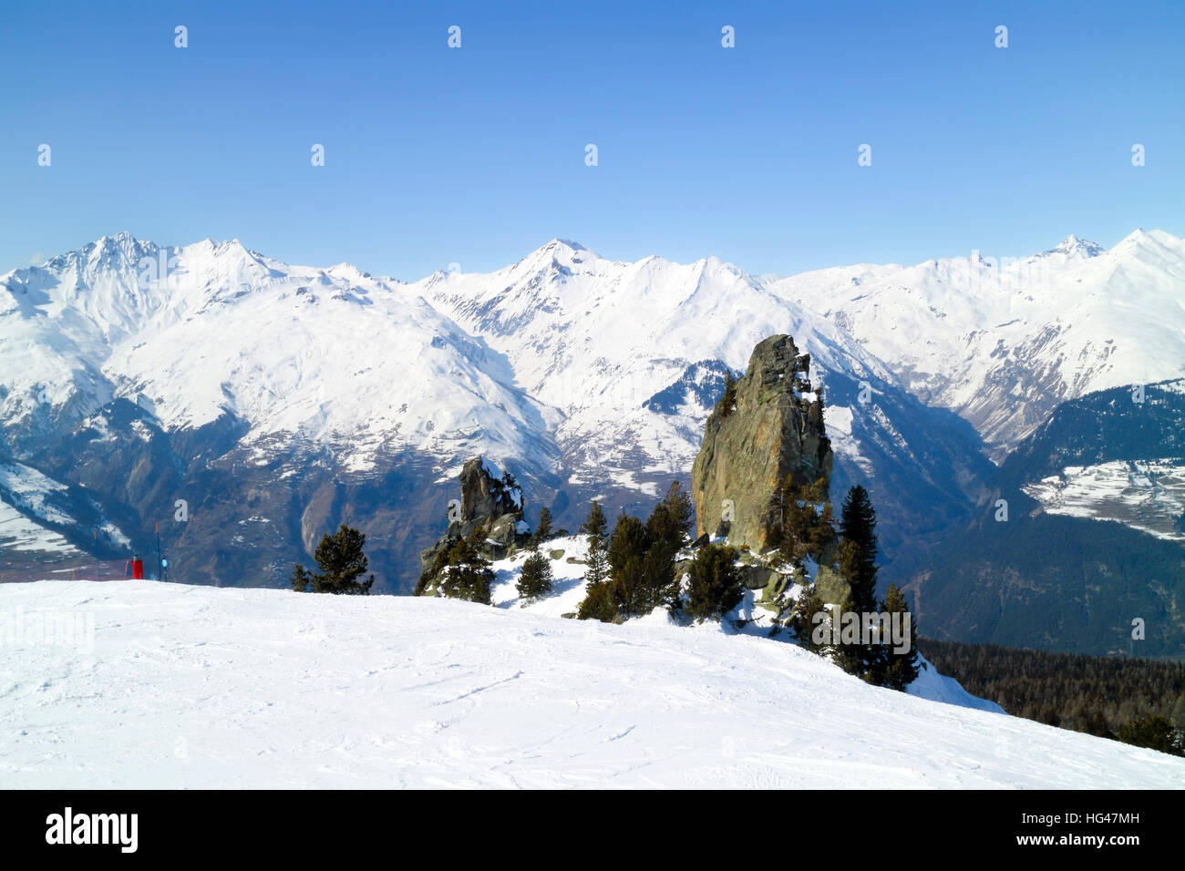 Rock surrounded by pine trees on a skiing slope on the background of alpine peaks in French Alps, Les Arcs, Paradiski - Stock Image