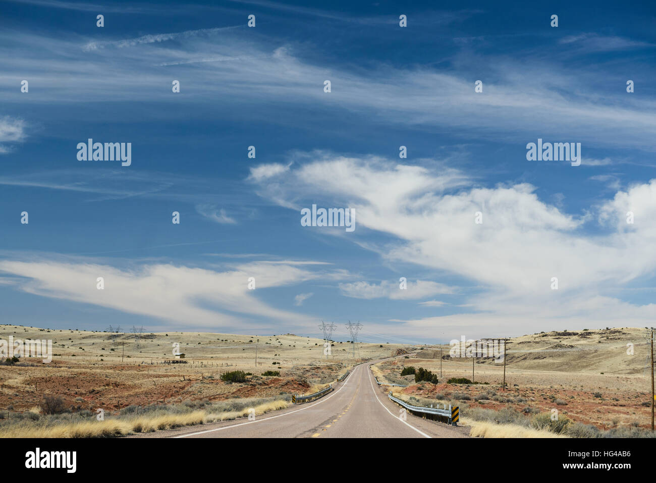 Small street in rural area of high desert in New Mexico, USA. Beautiful sky inspiring. - Stock Image