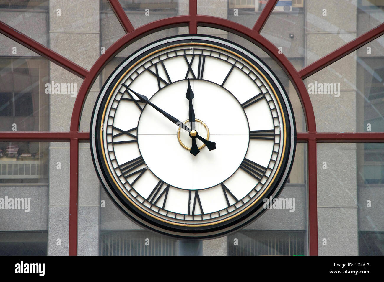 Clock with roman numerals for hours, hands at nine minutes to twelve o'clock on a glass wall, building in background - Stock Image