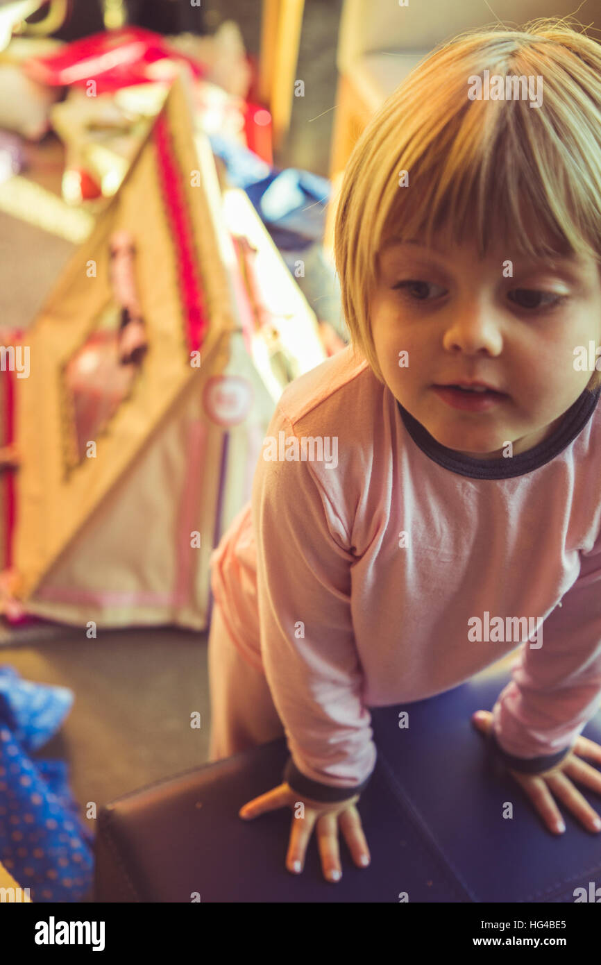 Little girl in her pink pajamas Christmas morning. - Stock Image