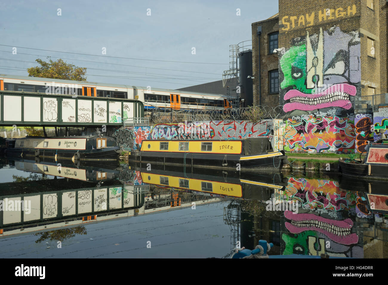 Overground train drives past canal by artists studios and warehouses in Hackney Wick, London, England, United Kingdom - Stock Image