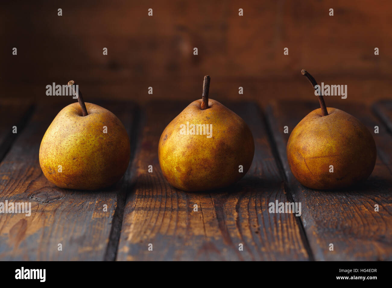 Brown ripe pears on a wooden table - Stock Image