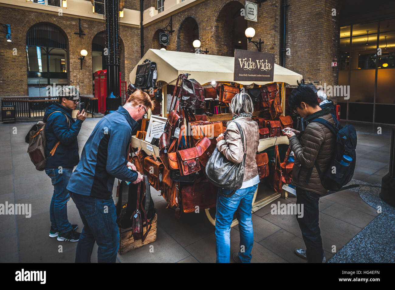 People around a stall with handmade purses and leather handbags and accessories in London - Stock Image