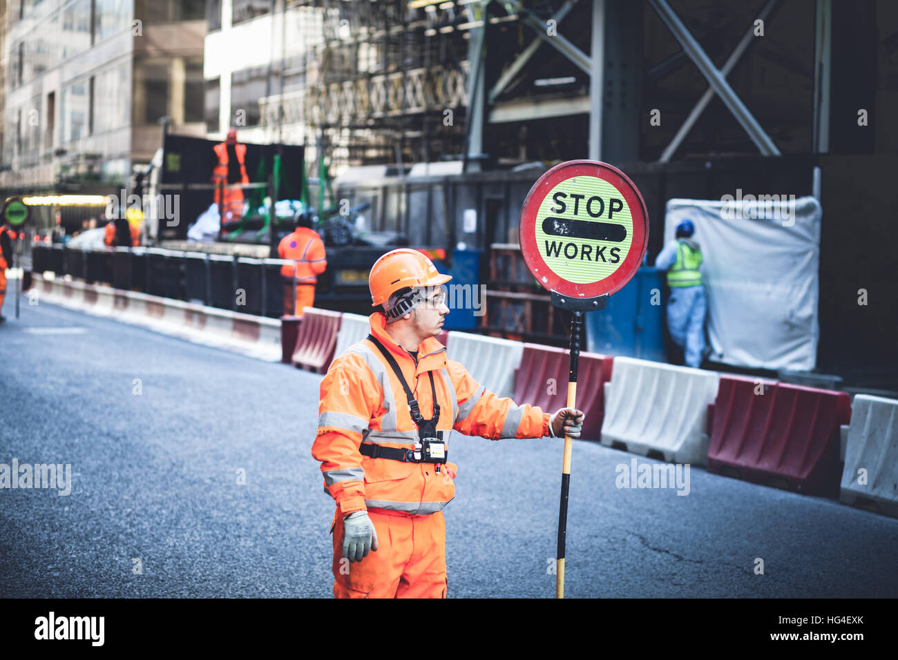 London UK, Workers blocking the road traffic for works with a STOP road sign Stock Photo