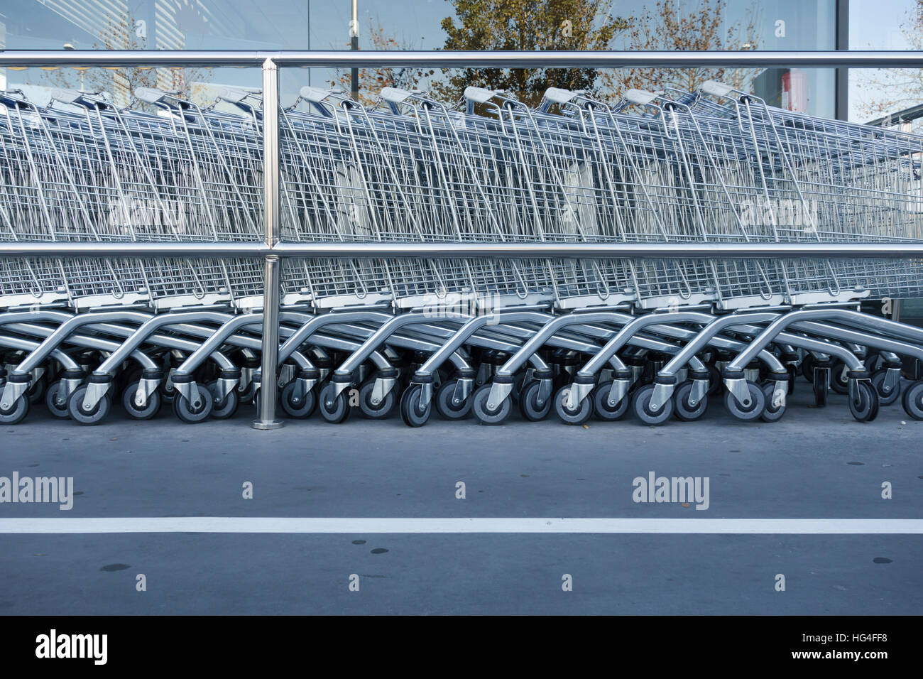 Supermarket carts in a row, in a shopping mall - Stock Image
