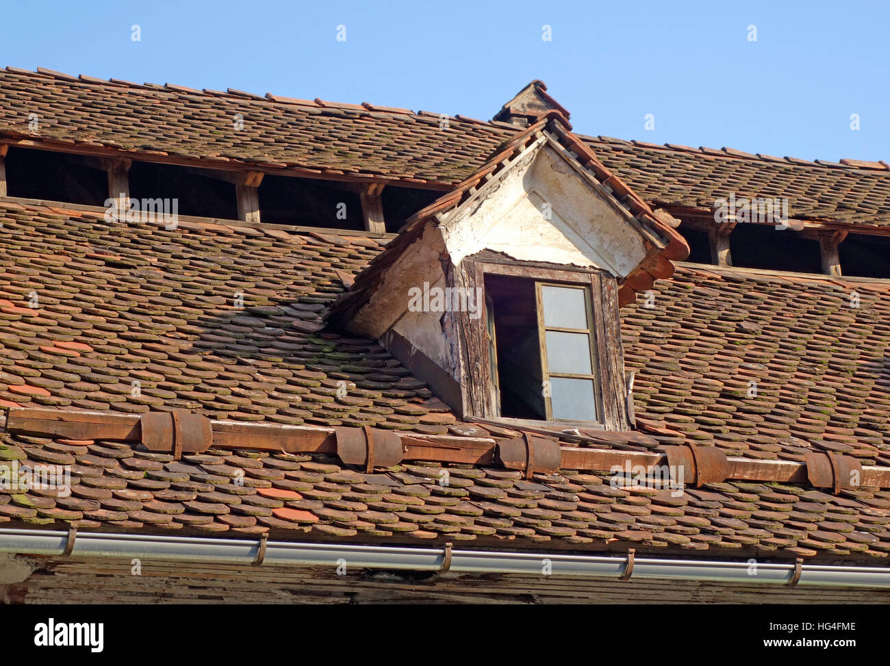 Medieval roof construction with window and openings for attic ventilation and snow guards - Stock Image