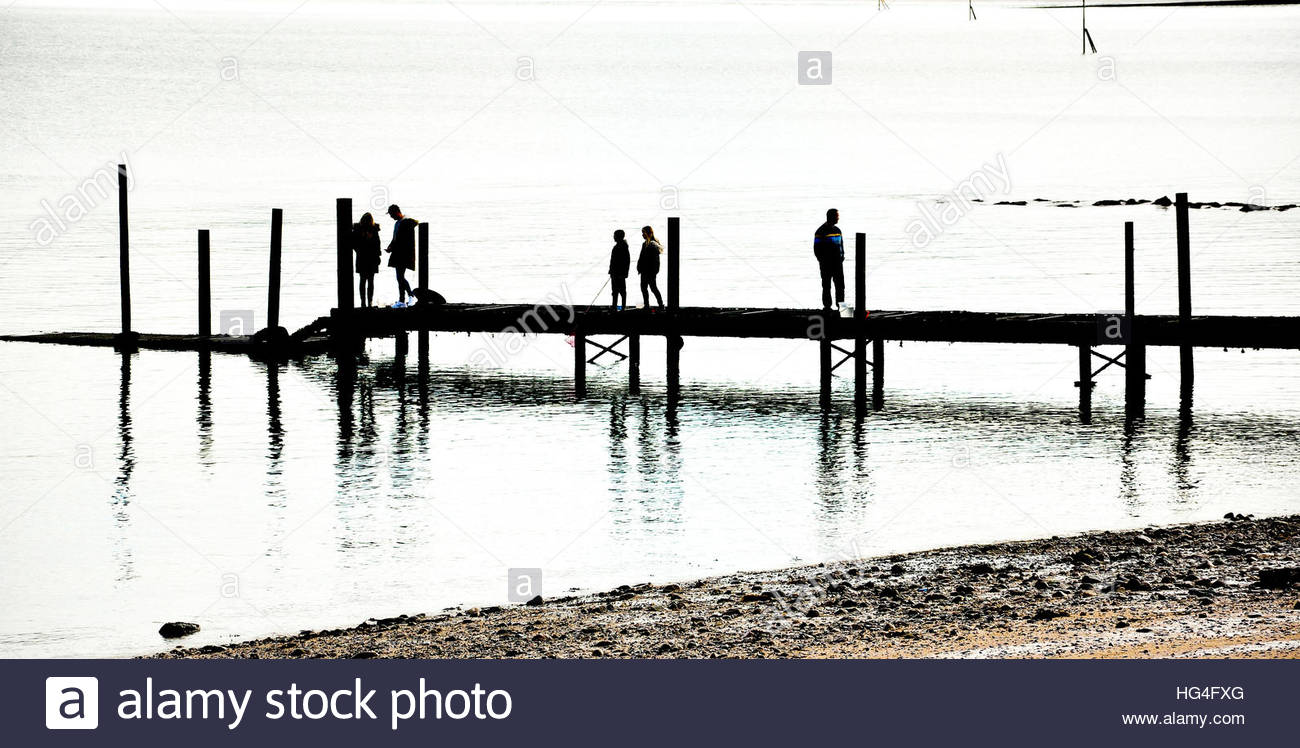A silhouette of people walking on a jetty at Rhos on Sea, Colwyn Bay in North Wales, UK. - Stock Image