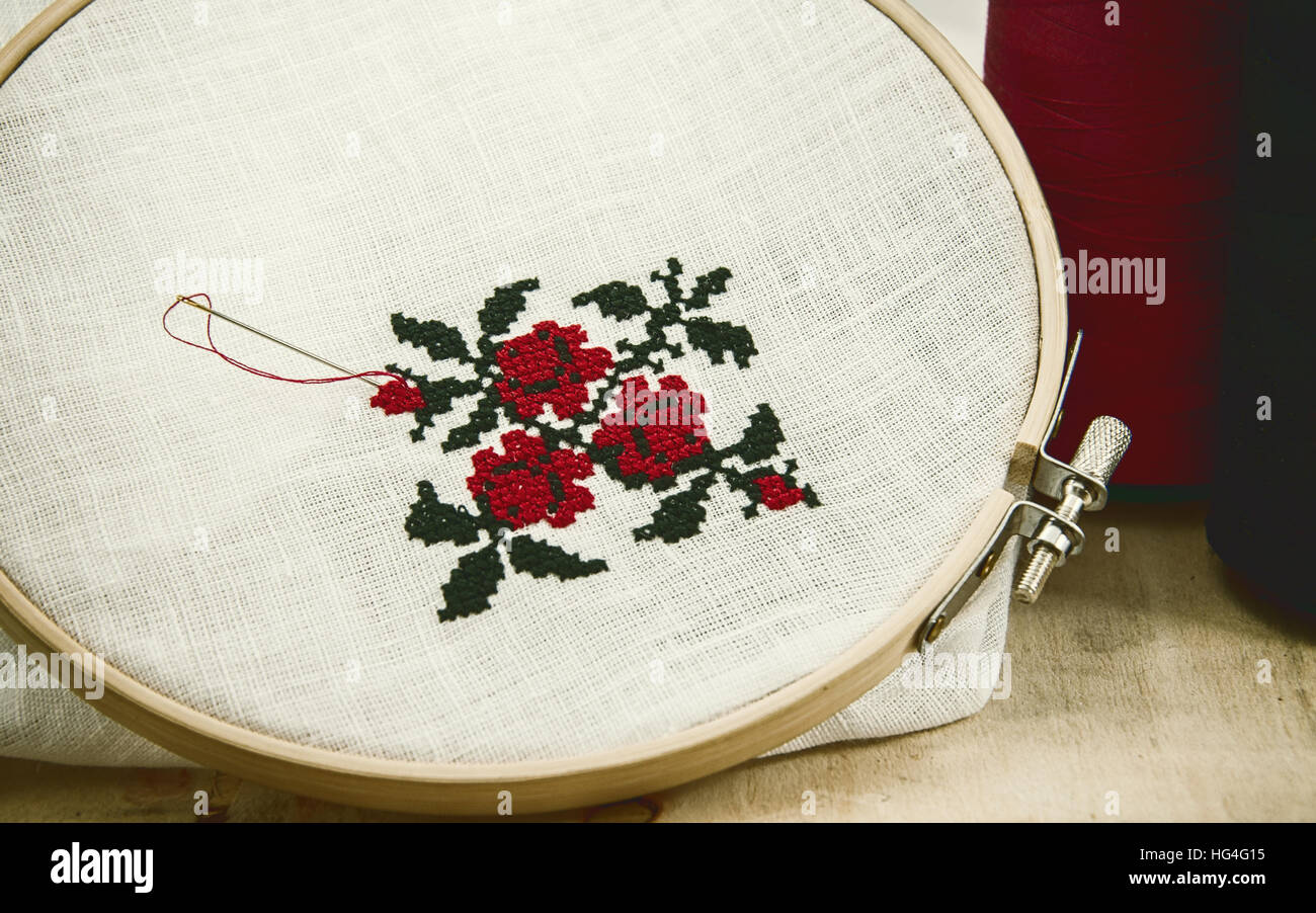 Hand embroidery cross-stitch flower ornament on a white fabric in ...
