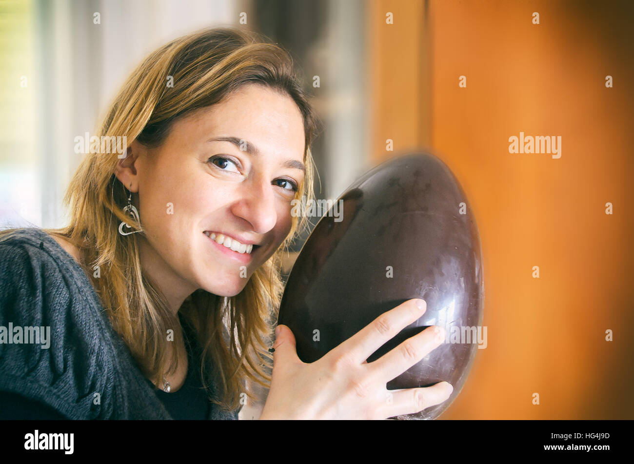 unwrapped easter egg woman happy smile portrait - Stock Image