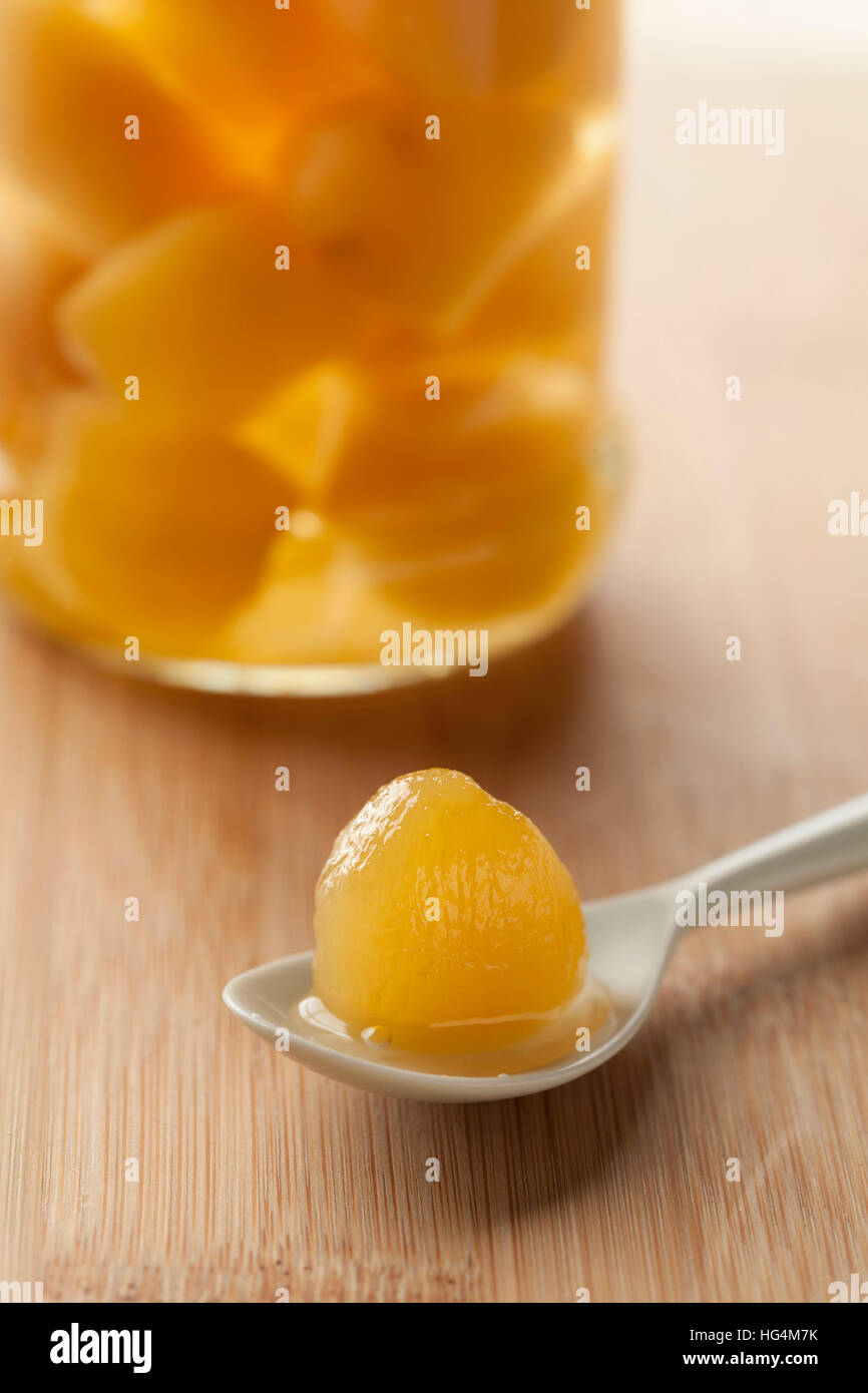 Stem ginger in syrup on a spoon - Stock Image