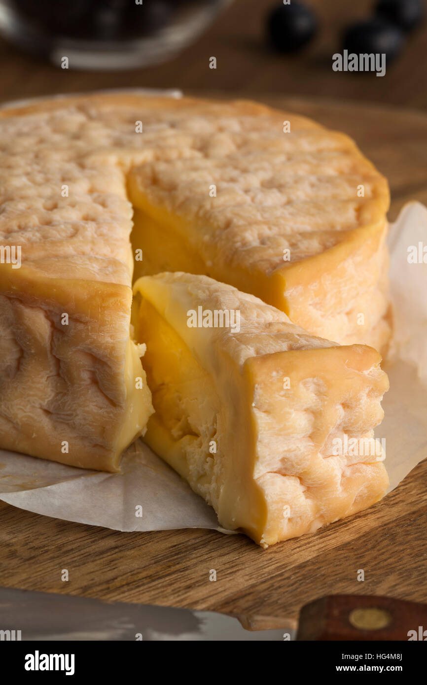 Creamy ripe Epoisses cheese and wedge close up - Stock Image