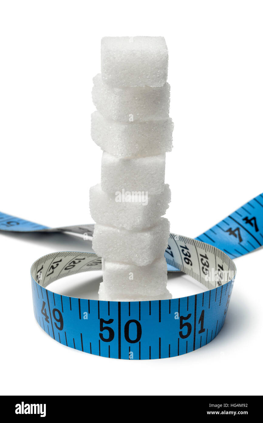 Tape measure around sugar cubes isolated on white background - Stock Image