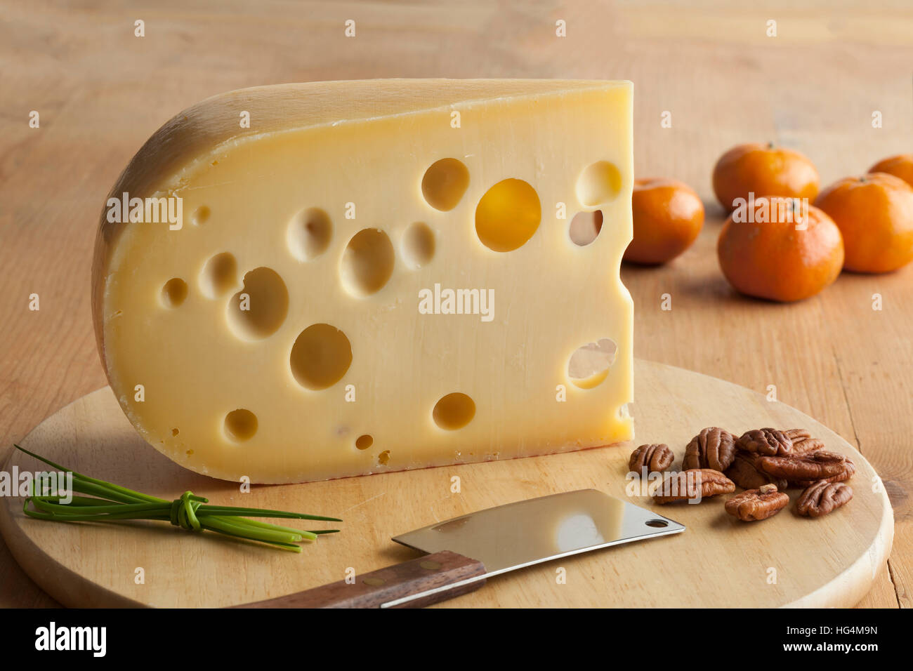 Piece of emmenthaler cheese on a cutting board with nuts and mandarins - Stock Image