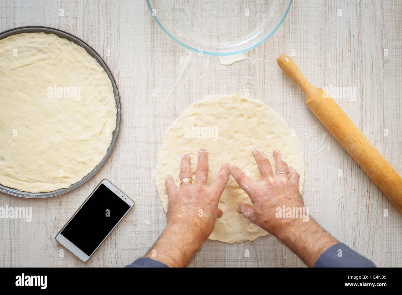 Man cooking dough for two pizzas on the wooden table horizontal - Stock Image