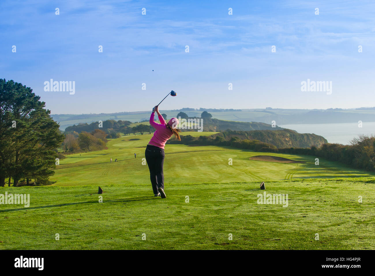 A young female golfer teeing off at the first hole. - Stock Image