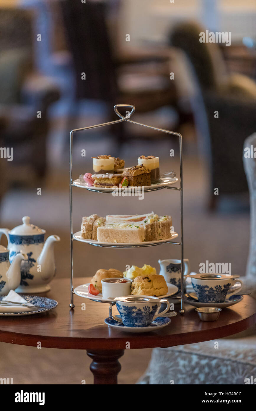 A Devon or Cornish cream tea with cakes and sandwiches. - Stock Image