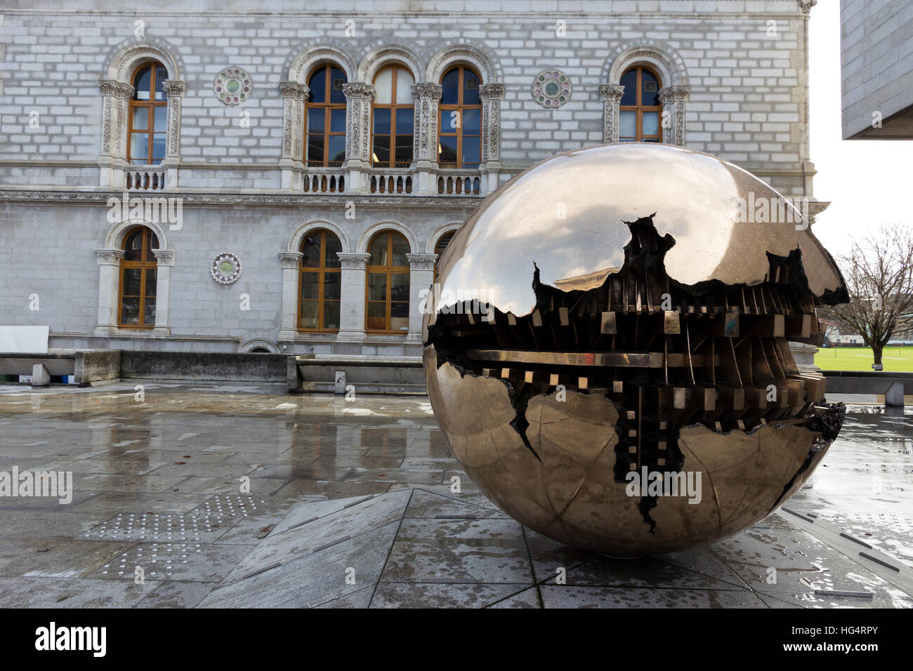 Abstract spherical metal sculpture on a courtyard of Trinity College, Dublin. - Stock Image