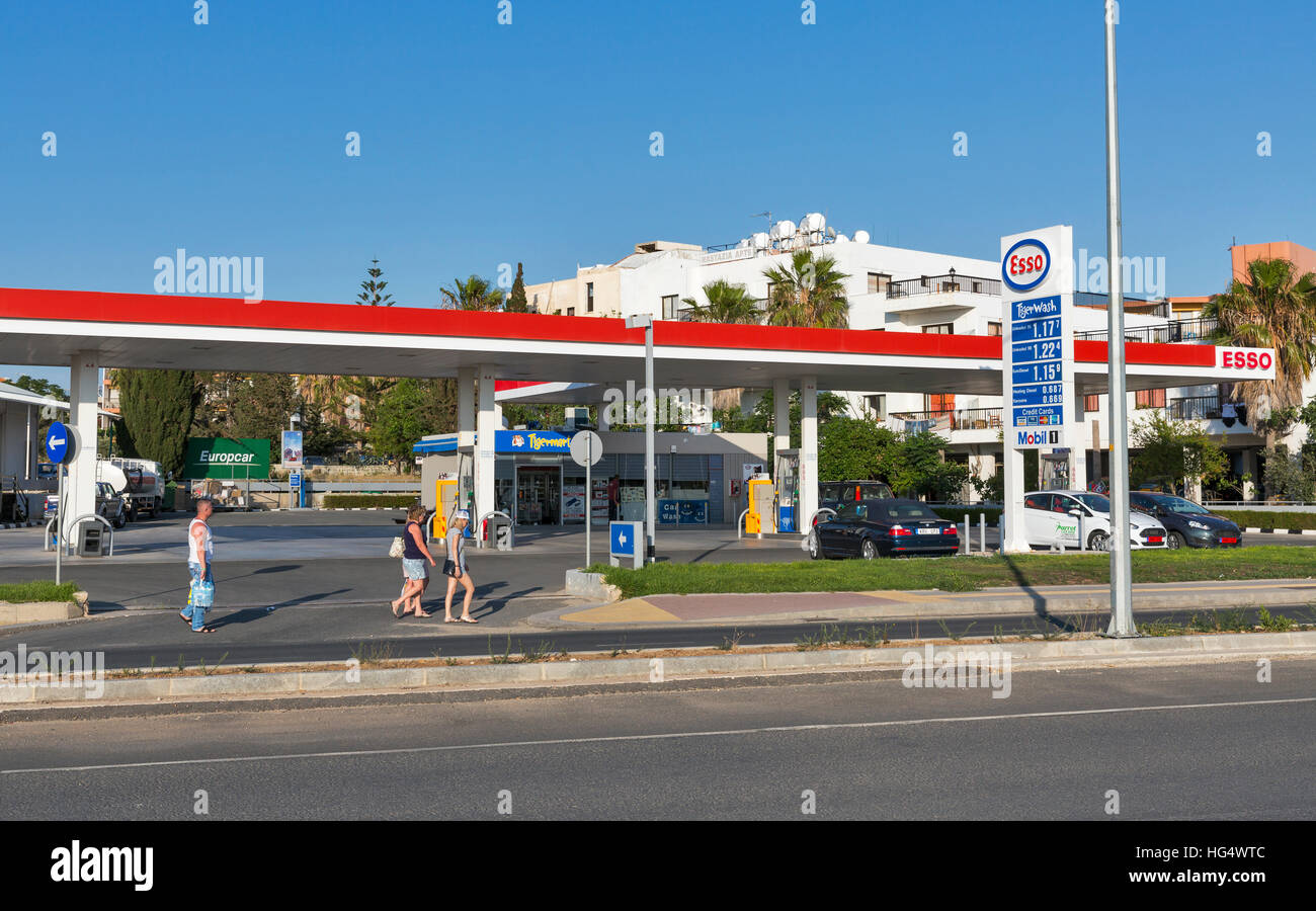 Unrecognized people walk in front of Esso gas station on the central street of the city. - Stock Image