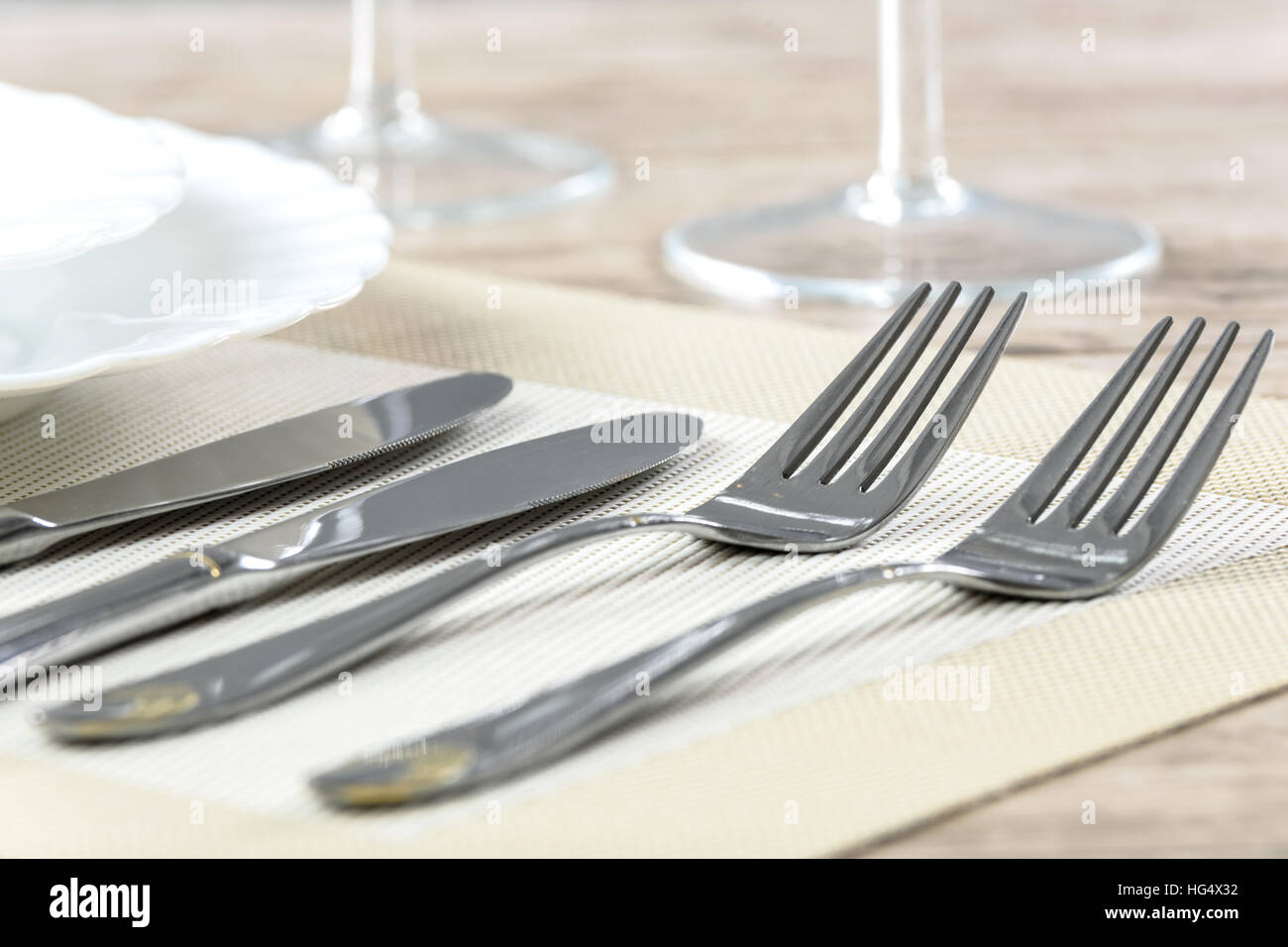 Elegant restaurant table setting with plates cutlery and stemware on a wooden table & Elegant restaurant table setting with plates cutlery and stemware on ...