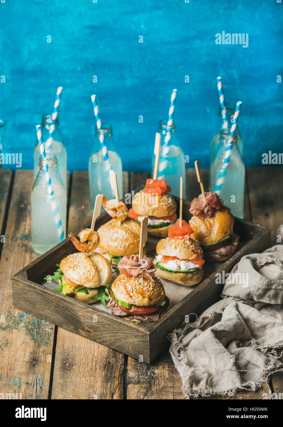 Homemade burgers in wooden tray and lemonade in bottles - Stock Image