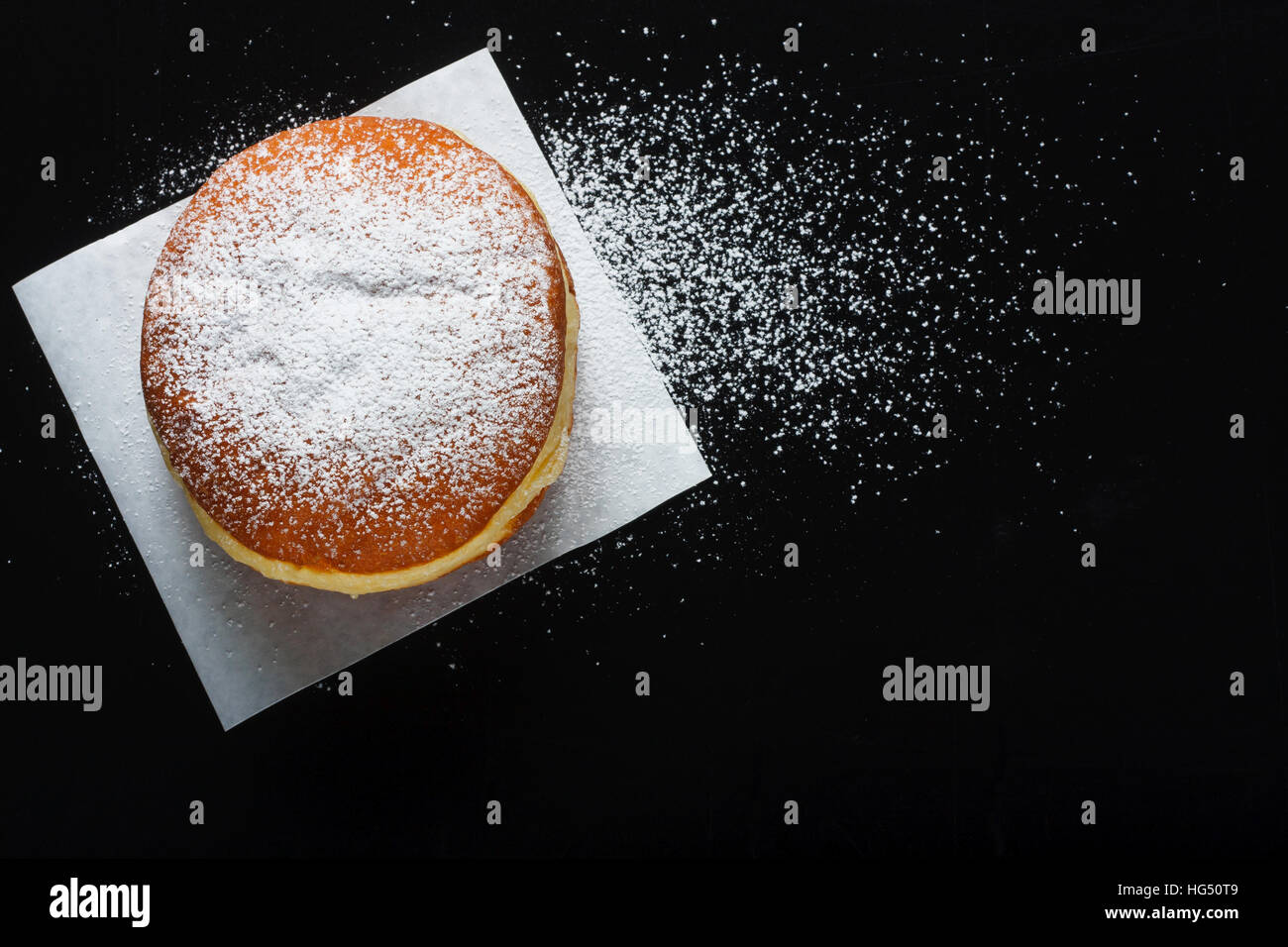 Donut and powdered sugar on dark background - Stock Image