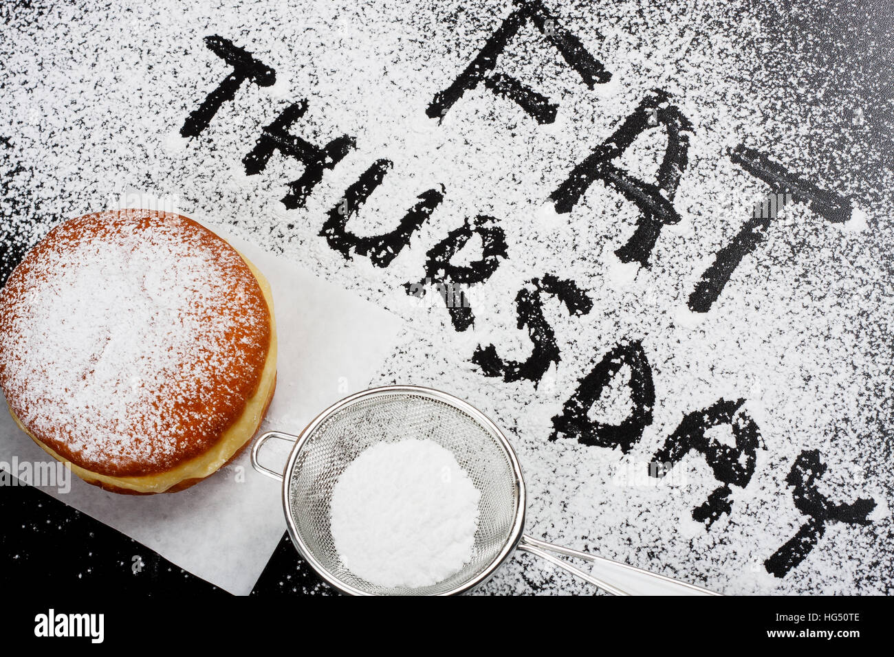 Fat Thursday. Donut and powdered sugar on dark background - Stock Image