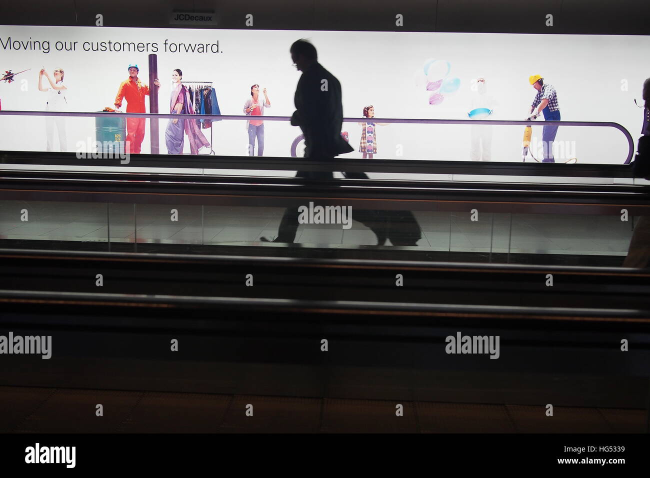 man rushing on moving walkway at an airport - Stock Image