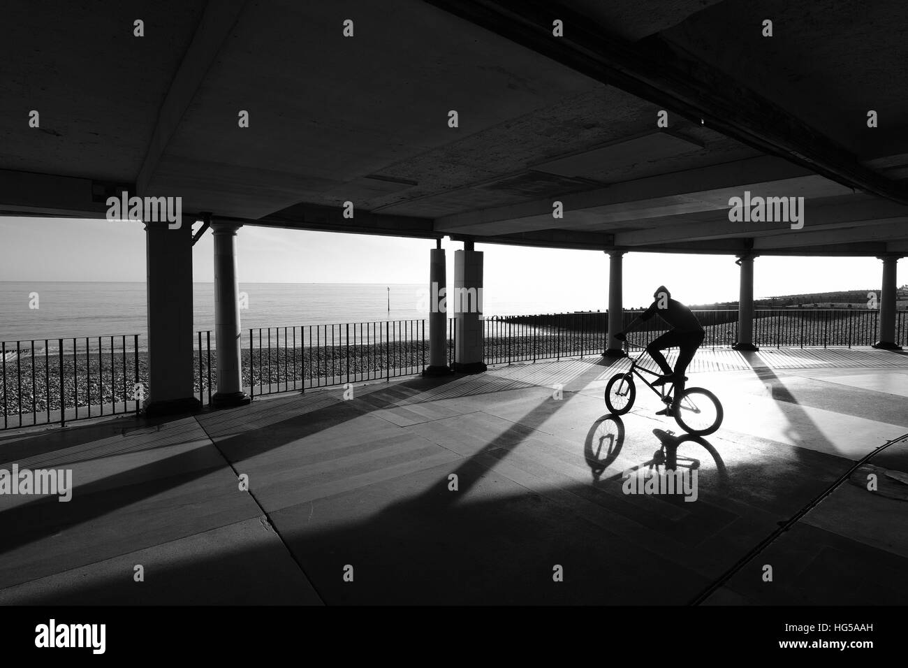 Silhouette of boy on a bike Eastbourne Bandstand - Stock Image