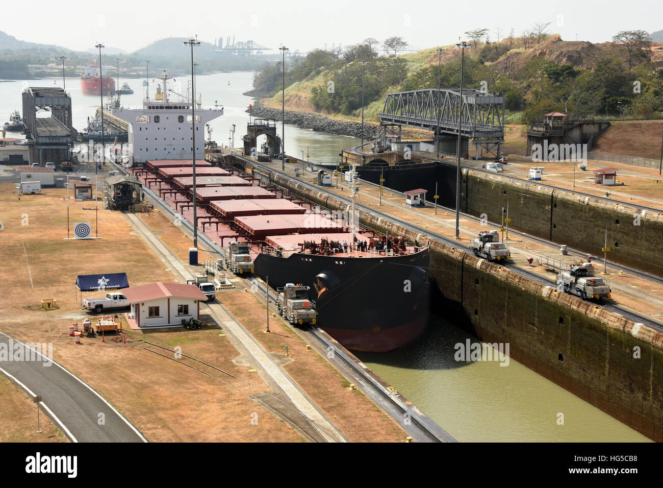 Electric mules guiding Panamax ship through Miraflores Locks on the Panama Canal, Panama, Central America - Stock Image