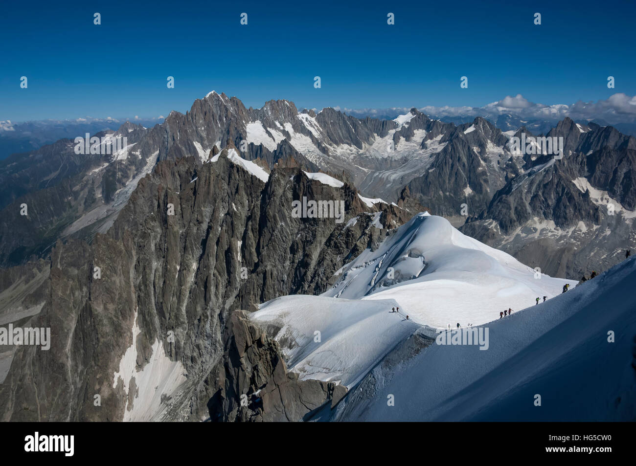 Climbers on a snowfield approaching the Aiguile du Midi, 3842m, Graian Alps, Chamonix, Haute Savoie, French Alps, - Stock Image