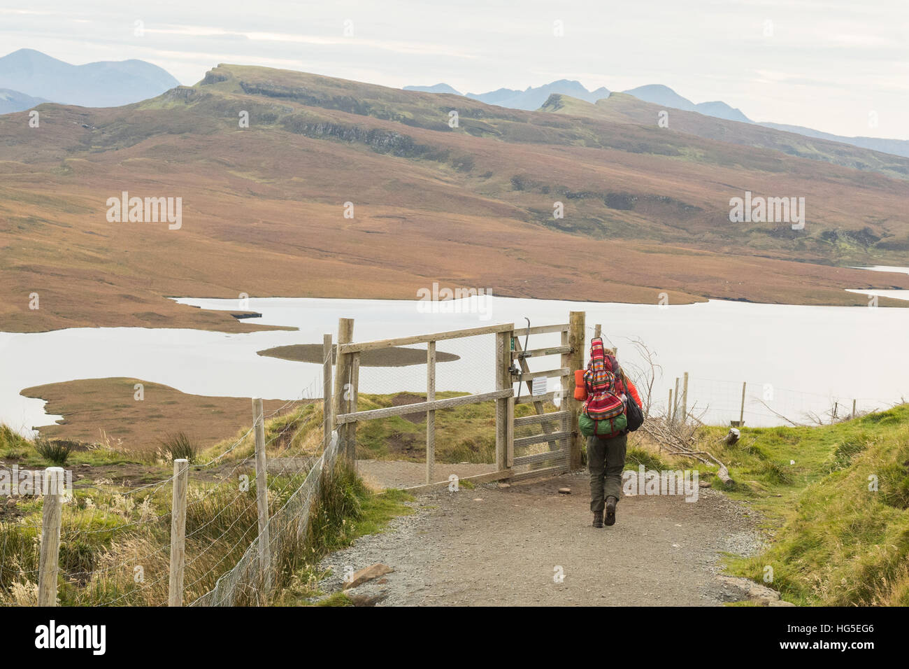 solitary female hiker traveller carrying guitar on back descending from the Old Man of Storr, Isle of Skye, Scotland - Stock Image