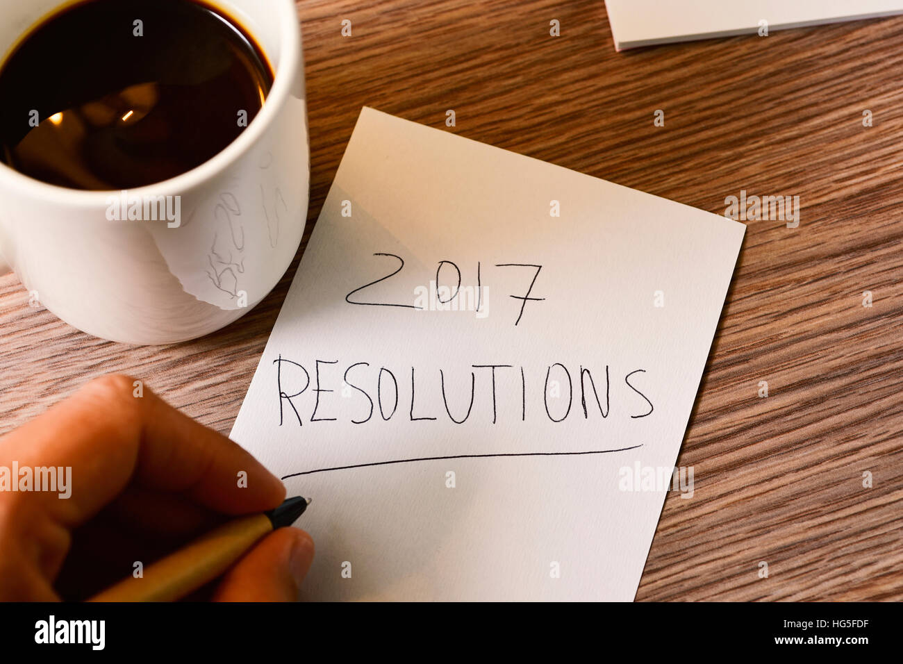closeup of a young caucasian man with a pen in his hand writing the text 2017 resolutions in a piece of paper, on - Stock Image