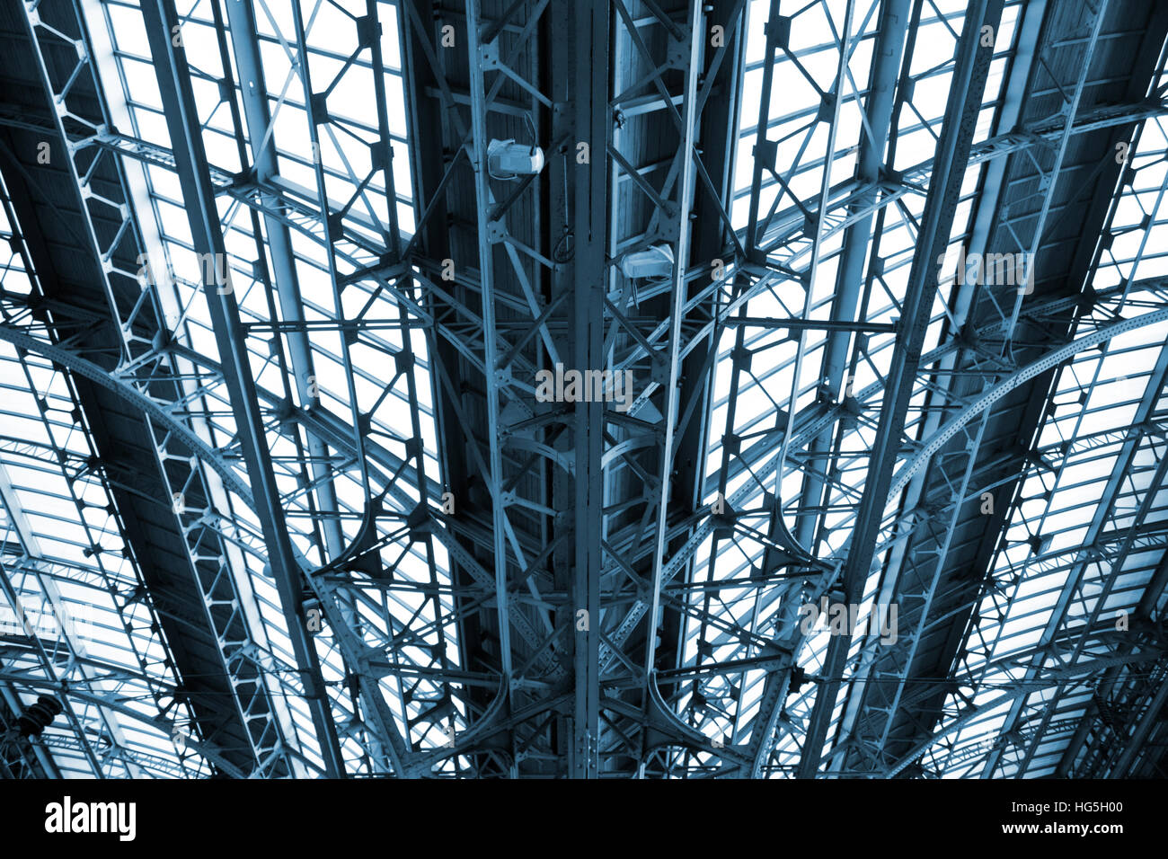 Railway construction canopy. A detail of the glass roof at the  railway station ,blue toning - Stock Image
