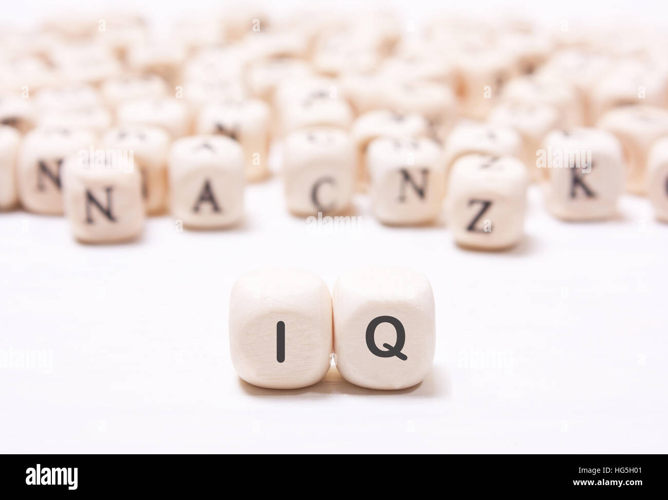 The word 'IQ' on the white  dice on a background of blurred letters. The concept of the mind, the intellect - Stock Image