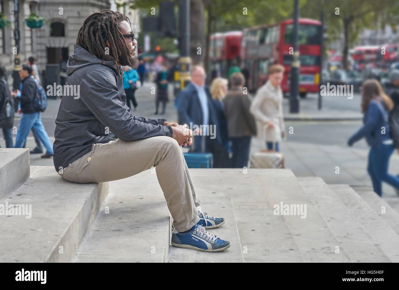 black man.  Man contemplating.   dreadlocks.  rastafarian.   Alone in the city. - Stock Image