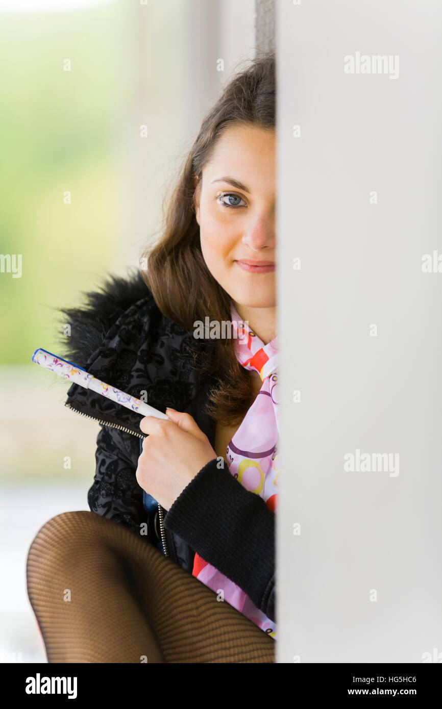 c03f6cee219c Schoolgirl peeking one eye behind wall corner looking at camera eyes-contact  serious holding notepad
