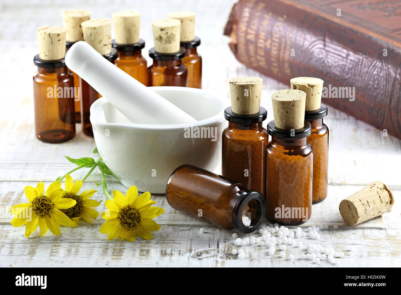 homeopathic arnica pills in brown glass bottles on wooden table - Stock Image