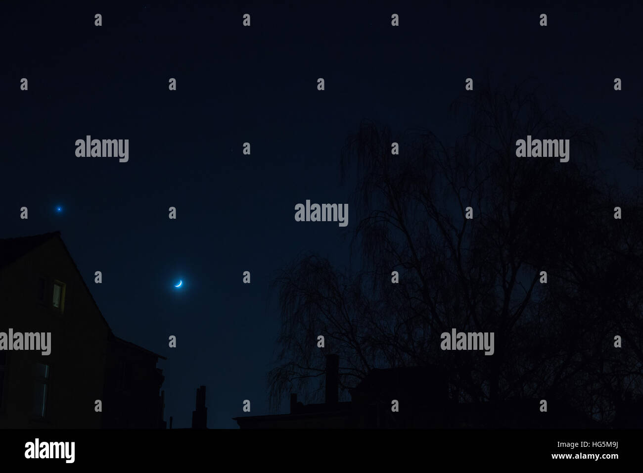Suburban backstreet nightshot with new moon and planet venus star over building's roof and tree shadow - Stock Image
